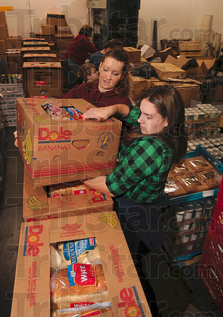 Tribune-Star/Joseph C. Garza<br /> Another sort of holiday packing: Benita Wilkerson and Abigail Collier stack finished baskets Wednesday at the Tribune-Star Production Center.