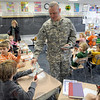 Cash for class: Army Master Sgt. John Plasse hands out 10,000.00 Afghanis to each of the students in Jan Greulach's class at Lost Creek Elementary School Monday morning. The bills are no longer in circulation and would be equal to about $500 dollars U.S.
