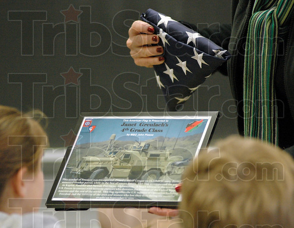 Detail: Lost Creek Elementary School 4th grade teacher Jan Greulach shows a certificate presented to her class by Army Master Sgt. John Plasse during his visit Monday morning. The Flag she's holding was flow during a combat mission in Afghanistan by Plasse's unit.