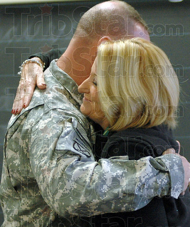 Homecomng hug: Lost Creek Elementary School 4th grade teacher Jan Greulach gives a welcoming hug to Master Sgt. John Plasse as he visits her classroom Monday morning.