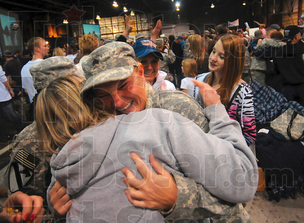 Back home in Indiana: Sgt. Geneva York of Terre Haute receives a hug from Marnie Newman of Terre Haute after York and her fellow soldiers from the 138th Quartermaster Company arrived at Building 9 at Sout Field in Indianapolis Monday.