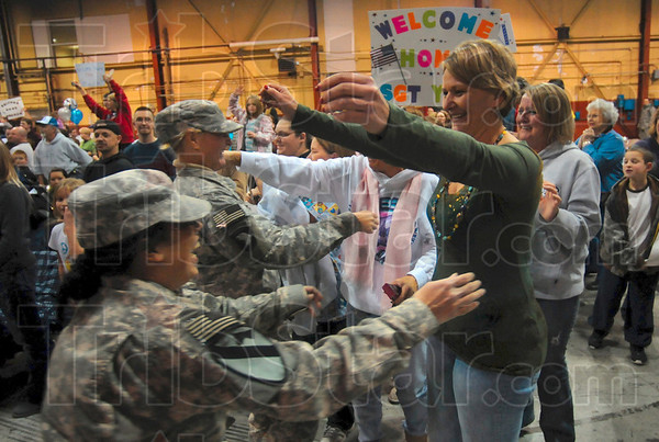 Hug for a hero: Karen Galloway of Terre Haute greets Specialist Mary Tarrh of the 138th Quartermaster Company after the company's arrival Monday in Building 9 at Stout Field in Indianapolis.