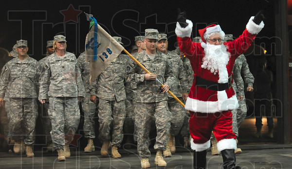 Led by the jolly ol' elf himself: Santa Claus leads members of the 138th Quartermaster Company into Building 9 at Stout Field in Indianapolis Monday.