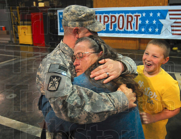 Too long since the last hug: Wilma Barnes of Terre Haute takes her time in hugging her son, Sgt. Dean Barnes, as Dean's nephew, Bailey Barnes, 11, looks on Monday in Building 9 at Stout Field in Indianapolis.