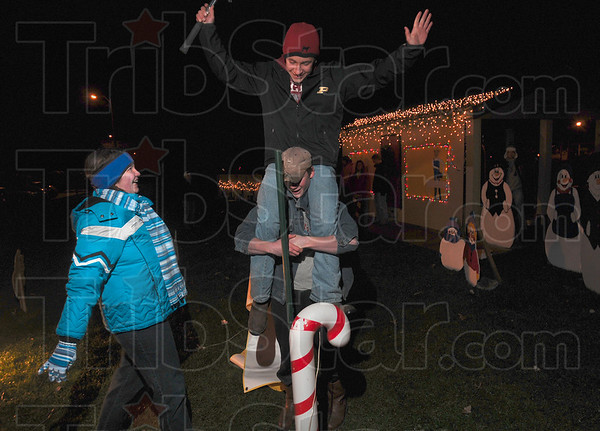 Tribune-Star/Joseph C. Garza<br /> Teamwork: Vigo County 4H Junior Leaders member Elizabeth Tock celebrates with fellow members Matt Marion and Jesse Farmer after they were able to hammer a pole in the ground for the group's display Monday in Deming Park.
