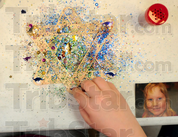 Tribune-Star/Joseph C. Garza<br /> Seven-year-old Zoe Pitts makes an ornament at the Terre Haute Children's Museum Tuesday evening during the museum's Holiday Drop-N-Shop program. Pitts was pressing down on the piece so it could dry in its proper place and then add her own photo.