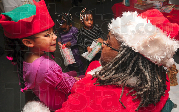 Tribune-Star/Joseph C. Garza<br /> Her list: Lylah Hickson, 6, lets Santa Claus, a.k.a. Jeff Lorick, know what she really wants for Christmas (a computer) during the Greater Terre Haute NAACP Youth Council's holiday celebration Tuesday in the Prince Hall Masonic Lodge.
