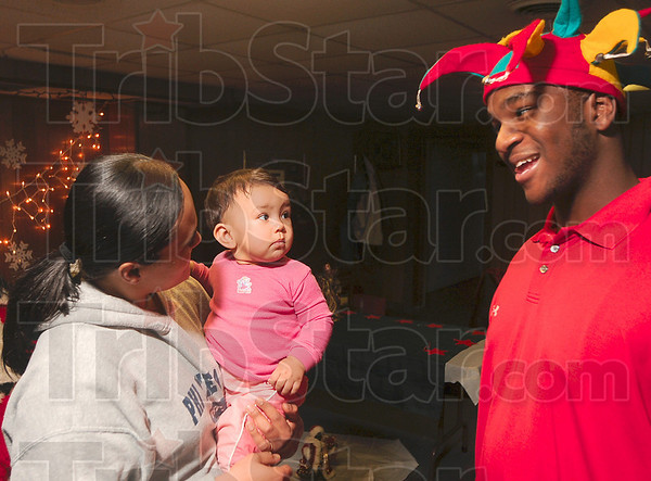 """Tribune-Star/Joseph C. Garza<br /> Not sure about this Santa's helper: Ten-month-old Tianna Sluder keeps an eye on """"Santa's helper"""" Marlin Hill, a Terre Haute North junior and Greater Terre Haute NAACP Youth Council member, Tuesday during the council's holiday celebration at Prince Hall Masonic Lodge. Sluder was being held by Stacy Hurtt."""