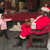 Tribune-Star/Joseph C. Garza<br /> It's Santa!: Three-year-old Riquel Coleman reaches out to Santa Claus during his appearance at the Prince Hall Masonic Lodge Tuesday as part of the Greater Terre Haute NAACP Youth Council's holiday celebration.