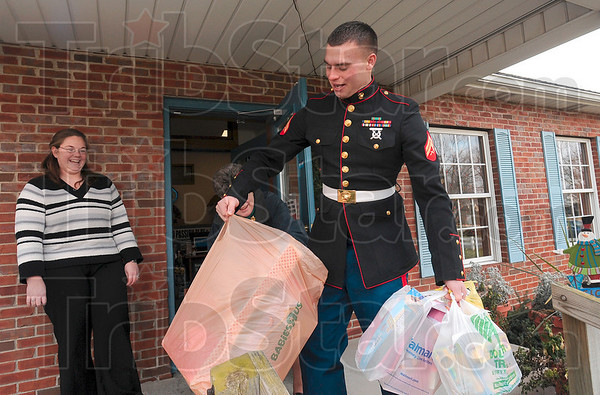 Tribune-Star/Joseph C. Garza<br /> Not too heavy for this Marine: Cpl. Benjamin Mitchell of 3rd Battalion, 24th Marines, Kilo Co., carries a load of toys from the front porch of Turner Coaches Tuesday off of Margaret Avenue. Looking on is Turner employee, Stacey Ford, as co-worker Janet Knight helps Mitchell balance his load. Mitchell and fellow marine, Sgt. Damon Ward, were collecting toys for the Toys for Tots Program Tuesday morning.