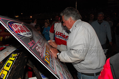 Dixie Speedway promoter Mickey Swims signs the Victory Lane check for Ray Cook