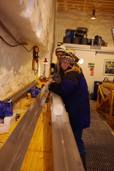 An ice core is carried to the core buffer.<br /> <br /> En iskerne bæres ind på kernelageret<br /> Photo: Sune Olander Rasmussen