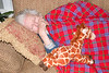 When Katie and Gracie discovered Mimi asleep on the sofa, they gently covered her with a Maasai blanket and snuggled the giraffe up next to her for companionship!