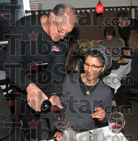 nal Service: Rose-Hulman president Gerald Jakubowski pours wine for Jude Ciancone as he waits tables at J. Ford's Black Angus Thursday night.