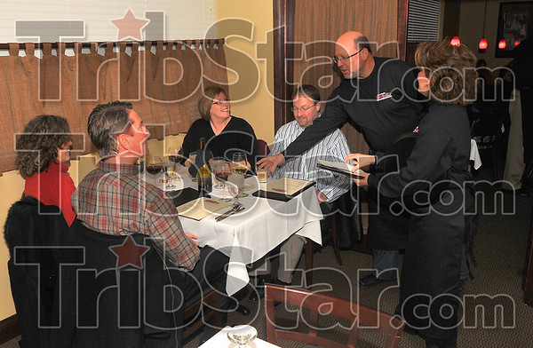 At your service: Steve and Lori Danielson, along with Jamey aned Jennifer Kirsch are tended to by Gary Morris and Marla DeHart. They were at J. Ford's Black Angus, who hosted a fundraiser for the United Way.