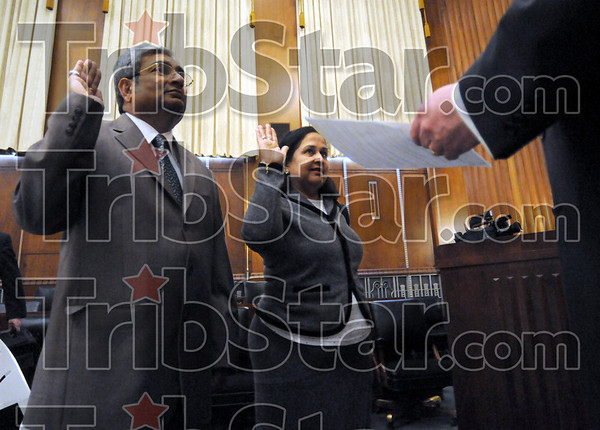 Better late: Mahesh Modi and wife Aruna Modi take the oath of citizenship from Federal Judge Craig McKee after arriving late to the original swearing-in ceremony Thursday afternoon.
