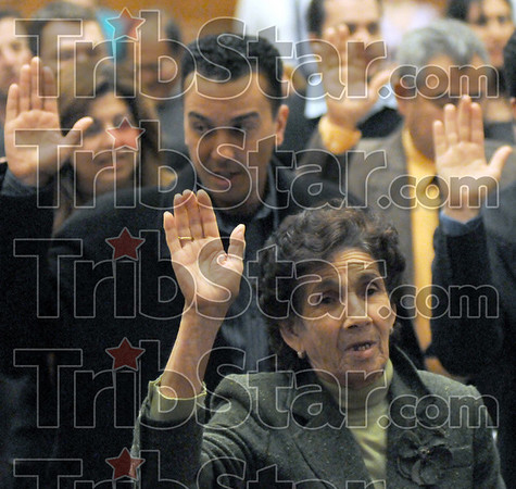 Oldest: Maria Elena Garibay raises her hand to be sworn-in as the oldest naturalized citizen during Thursday's ceremony at the Federal Courthouse. She is from Mexico.