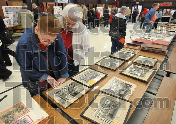 Tribune-Star/Joseph C. Garza<br /> Looking back at Tiger track: Paris, Ill., High School 1956 graduate Pauline Good and Jane Erwin, a 1953 Newport, Ind., High School graduate look over a Paris High School track team photo from the 1950s during the school's 100th anniversary celebration Sunday in Paris.