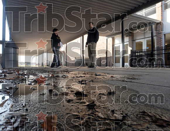 Drainage: Chauncey Rose principal Claire Marchese and Mick Newport look at a drainage problem under the canopy between the school and gymnasium Friday afternoon.