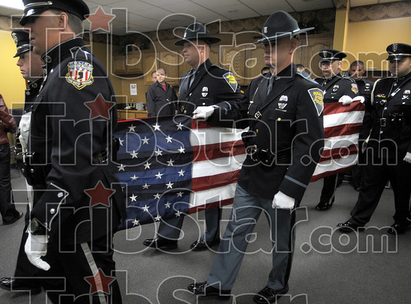 Honor Guard: City and State police officers carry a Flag during a ceremony honoring two deceased K-9s at the Terre Haute Police Headquarters Friday afternoon.