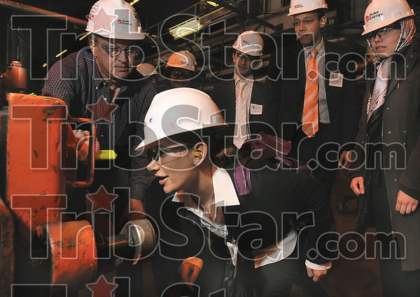 Tribune-Star/Joseph C. Garza<br /> How it works: University of Illinois graduate student Arzu Karaarslan of Turkey gets a closer look into one of the feeders at the Cayuga Duke Energy plant during a tour Friday led by plant manager John Frazier, left.