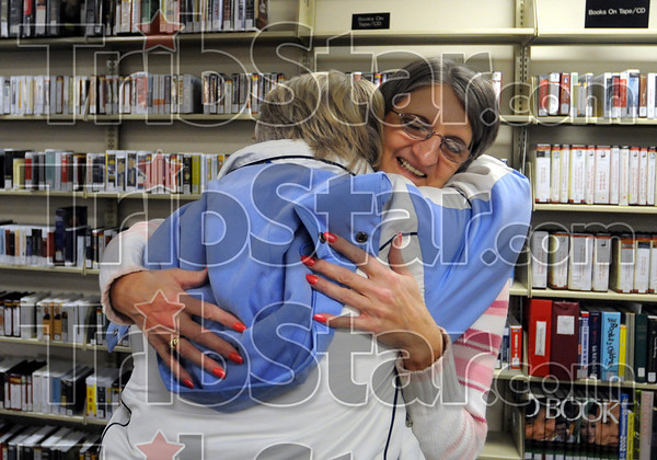 Gonna miss ya: Library patron Monica Waller gives Meadows library clerk Judy Johnson a hug at closing Friday evening as the branch closed its doors for the final time.