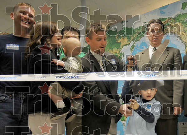 Ribbon-cutting: Members of the Roberts families prepare to cut the ribbon during Friday's grand-opening of the One Planet Solar/Wind business located at 2350 Wabash Ave.