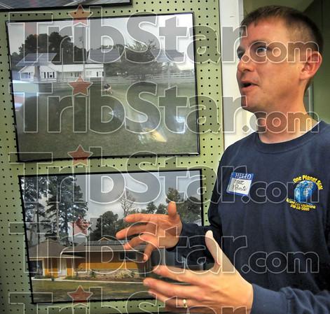 Solar talk: Matt Roberts talks solar energy with Tribune-Star reporter Arthur Foulkes during the grand-opening of the eastside business Friday morning.