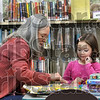 "Tribune-Star/Joseph C. Garza<br /> Learning at the library: Peggy Esau plays a game of ""Trouble"" with her granddaughter, Megan Esau, 5, at the Meadows branch of the Vigo County Public Library. Peggy uses the game to help her granddaughter count."