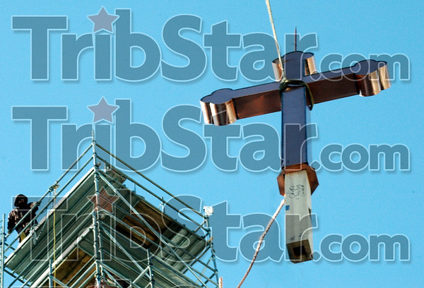 Going up: A construction worker atop the scaffolding around the steeple of the St. Stephen's Church waits for the arrival of the new cross that will top the structure Wednesday morning.