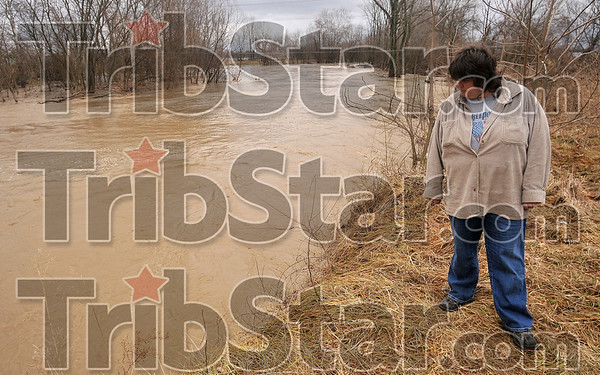 Tribune-Star/Joseph C. Garza<br /> Riding out the storm: Toad Hop resident Mary Johnson watches as water rapidly flows through Sugar Creek Wednesday. Johnson, 38, has lived in the small community for 36 years.