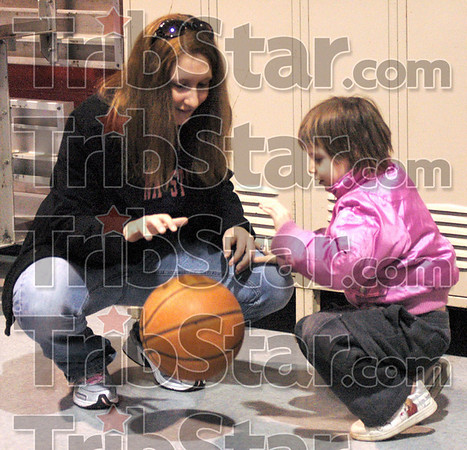 Bounce: Indiana State University student Cecee Emmons bounces a ball with a young girl Tuesday evening as part of her in service project at Ryves Hall.