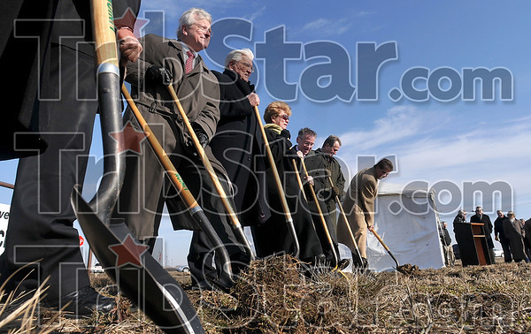 Tribune-Star/Joseph C. Garza<br /> Breaking for business: Curt Brighton, left, of Hulman & Co. and a member of the First Financial Corporation board and Don Smith, president and chairman of First Financial Corporation, along with other guests, ceremoniously break the ground at 2425 South State Road 46 Tuesday. The ground breaking ceremony was for the company's 49th banking center.