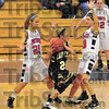 Trapped: Lady Wildcat Mandy Kelly looks for an open teammate while Terre Haute North's Danielle Ketner(25) and Lindy Jones(10) try to stop her.