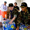 Ensign Smith and CDR Nwaba stack water cases in a first aid station.  Photo by LT Loren Rodgers.