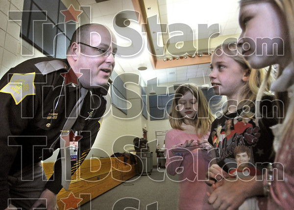 Cafeteria duty: Chief Deputy Greg Ewing of the Vigo Co. Sheriff's department takes time to chat with Sugar Grove second graders Brieanne Rutledge, Camilla Wilson and Heaven Briley as they go back to class after having lunch Thursday afternoon.