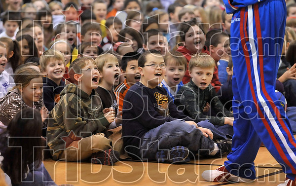 "Tribune-Star/Joseph C. Garza<br /> Loud and proud: Rio Grande Elementary School students, including second-graders Seth Bayless (in camo jacket) and C.J. Gilbert (center), cheer with their fellow male classmates during a cheering contest with Harlem Globetrotter Herbert "" Moo Moo"" Evans Thursday during Evans' appearance at the school."