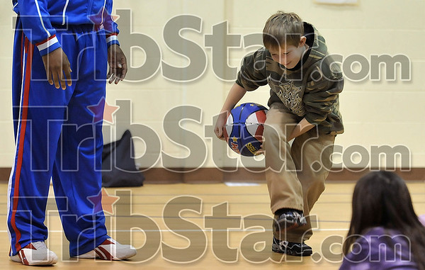 "Harder than it looks: Rio Grande Elementary School second-grader Seth Bayless tries his best to pass the ball between his legs as Harlem Globetrotter Herbert ""Moo Moo"" Evans looks on Thursday at the school."