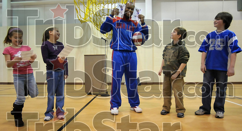 "Tribune-Star/Joseph C. Garza Muggin' mug shots: Harlem Globetrotter Herbert ""Moo Moo"" Evans shows off two autographed photos of himself before presenting them to Rio Grande Elementary School students Seth Bayless, right, and Kelland Sloan Thursday at the school. At left, are fellow Rio Grande students Isabella Fox and Shelby Calloway."