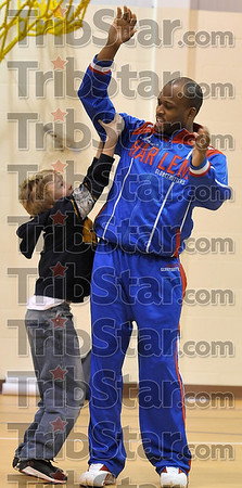 "Tribune-Star/Joseph C. Garza<br /> High five challenge: Rio Grande Elementary third-grader Parker Bray, 9, pulls down on the arm of Harlem Globetrotter Herbert ""Moo Moo"" Evans after Evans challenged Bray to a high five with his arm straight up in the air Thursday at the school."