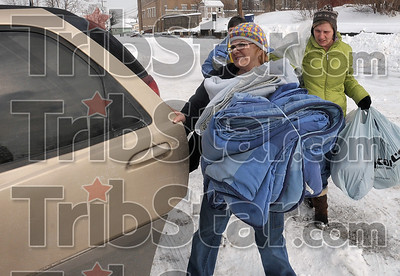 Tribune-Star/Joseph C. Garza Warm donations: Charlene Loudermilk, a Catholic Charities case manager, carries donated blankets to her car with help from Sandy Waldridge, director of community outreach with the Children's Bureau, and Indiana State social work student, Robbin Holmes, Thursday at the Mix 100.7 radio offices. The blankets were for the homeless that they met while doing the homeless count Thursday.