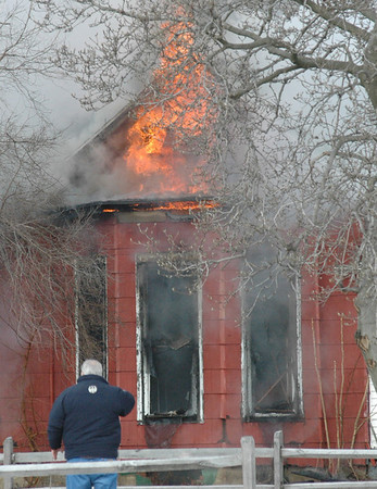Flames: Flames burst from the roof of a home in the 800 block of north ninth street Thursday afternoon. A Terre Haute building inspector watches from a distance.