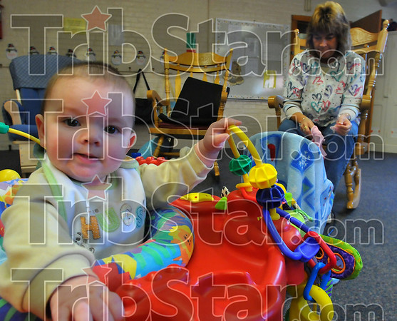 Cared for: Caeden Foltz plays in his walker in the Booker T. Washington School nursery while caregiver Christine Travioli tends to the needs of another child. The Alternatives to Learning and Living Nursery is funded in part by the United Way.