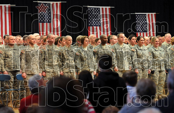 Appreciated: Members of the audience rise to their feet to applaud the soldiers of the 138th Quartermaster Support Company during the company's departure ceremony Friday at North Clay Middle School in Brazil.