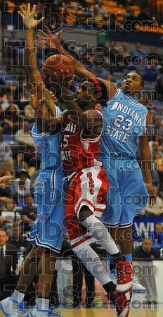 Redbird guardChamp Oguchi drives between Indiana State defenders  Isiah martin and Harry Marshall.