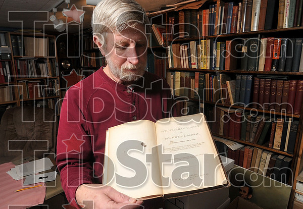 History in hand: Lincoln historian Chuck Hand displays a first edition of the 1858 Lincoln-Douglas debates which was printed in 1860 at his home Saturday in Paris, Ill.