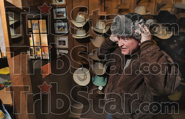 Tribune-Star/Joseph C. Garza<br /> The right fit: Jake Martin of Pekin, Ill., tries on a bomber hat at Boot City Wednesday. Martin had been looking for a bomber hat for some time before finding one at Boot City.