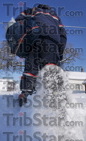 Tribune-Star/Joseph C. Garza<br /> Snowy delivery: Postal carrier Gary McGaha walks through the snow as he delivers mail on south Thirteenth Street Wednesday. The Postal Service has appealed to residents and businesses to clear the sidewalks for carriers.