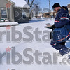 "Tribune-Star/Joseph C. Garza<br /> Neither snow, nor rain...: Postal carrier Gary McGaha tromps through a foot-high snow back as he makes his rounds on 13 and 1/2 Street Wednesday. McGaha says the snow ""brings out the kid in me."""