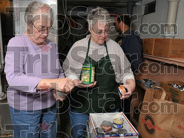 Tribune-Star/Joseph C. Garza<br /> More to cook with: Theresa Roetker and Ruth Myers of the St. PatrickÕs Soup Kitchen look over a large food donation coordinated by Terre Haute firefighter Don Seprodi Tuesday at the kitchen.